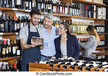 Salesman Showing Wine Information To Customers On Tablet...