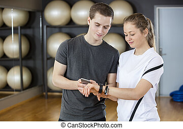 Friends Using Mobile Phone And Smart Watch In Gym - Smiling...