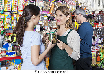 Smiling Saleswoman Looking At Customer Holding Dog Food Jar...