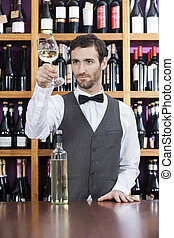 Bartender Examining White Wine In Glass At Shop - Young...