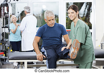 Female Nurse Assisting Senior Man In Leg Exercise - Smiling...