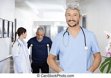 Doctor With Hands In Pockets Standing With Colleague And...