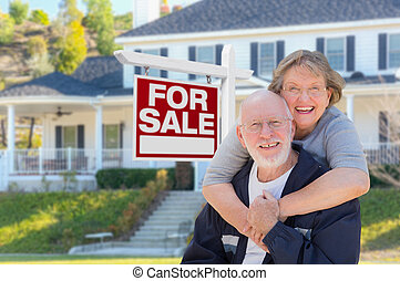 Senior Adult Couple in Front of Real Estate Sign, House