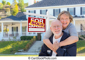 Senior Adult Couple in Front of Real Estate Sign, House -...