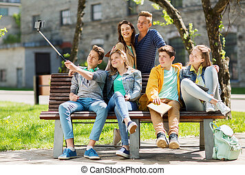 happy teenage students taking selfie by smartphone -...