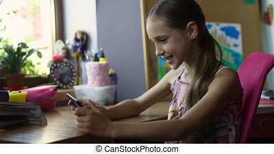 Little smiling schoolgirl sitting with smartphone playing games at desk in nursery