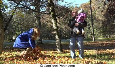 joyful couple with baby throw autumnal leaves in beautiful...