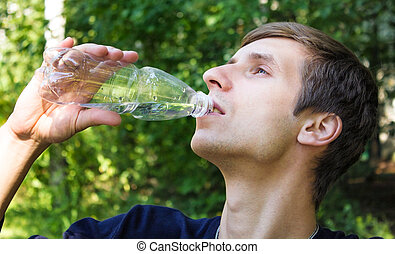 Young man drinks from the bottle