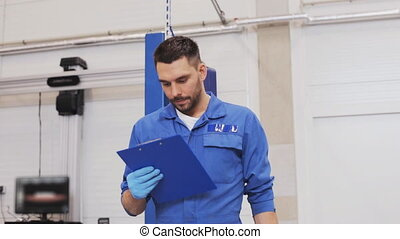mechanic man with clipboard at car workshop - car service,...