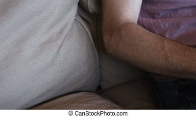Close up of man working with laptop computer and sitting on sofa at home
