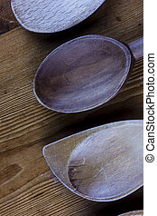 Close up of wooden spoon heads on a wood bench - Portrait...