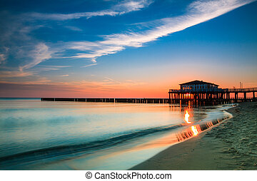 Restaurant at wooden pier on the baltic sea during sunrise....