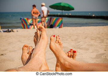 Couple feet on the beach In the background sunbathers with...