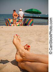 Women feet on the beach In the background sunbathers with...