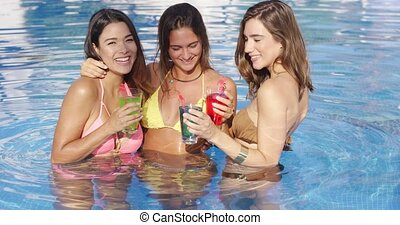 Three happy sexy female friends in a pool - Three happy sexy...