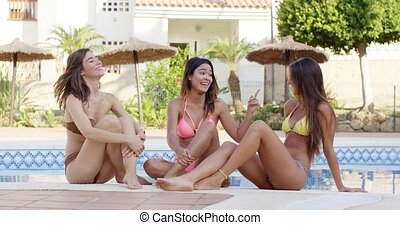 Three gorgeous young woman relaxing poolside in a tropical...