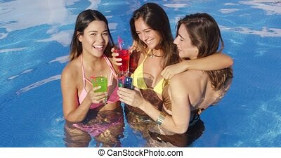 Three vivacious women enjoying cocktails in the cool water...