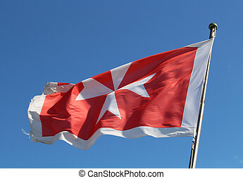 Maltese flag against a blue sky