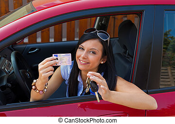 Woman with new car and driver\'s license and car keys