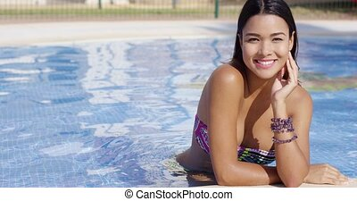 Smiling happy gorgeous young woman posing in the water at...