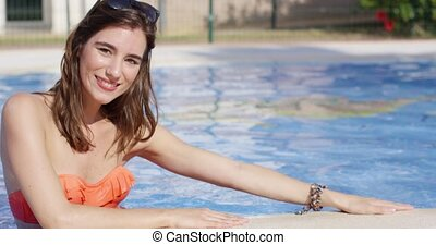 Attractive trendy young woman in a swimming pool