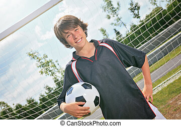 Soccer kid - A soccer player on the play field. The boy hold...