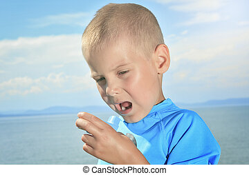 young sport boy using inhaler outside - A young boy having a...