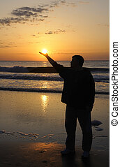 Man Holding Sun - A man holding his hand out to look as if...