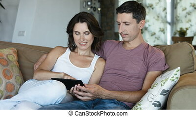 Charming couple of brunette wife and handsome husband couple websurfing on internet with touchpad