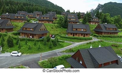 Wooden cottages in the middle of forest. Rocky hills. -...