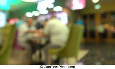 Blurred people eating fast food in mall food court. 4K bokeh...