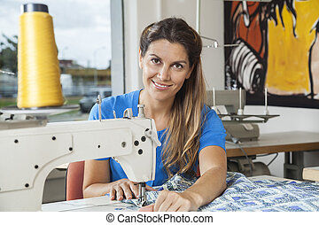Smiling Tailor Stitching Fabric At Workbench - Portrait of...