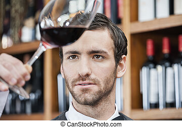 Bartender Examining Red Wine In Glass - Young bartender...
