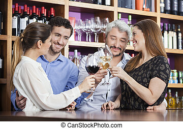 Male And Female Friends Toasting Wine Glasses - Happy male...