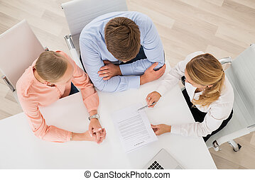 Estate Agent Explaining Document To Young Couple - High...