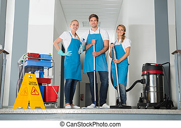 Portrait Of Janitors Holding Cleaning Equipments - Portrait...