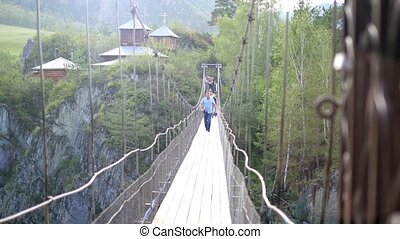people crossing suspension bridge - people cross a...