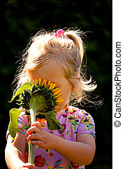 Child with a sun flower in the garden in summer