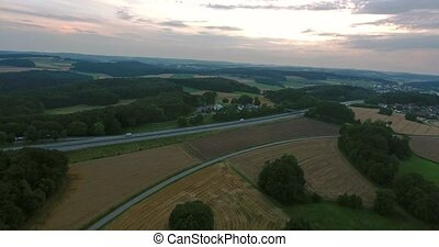 Aerial view of highway, forests and fields, village with houses