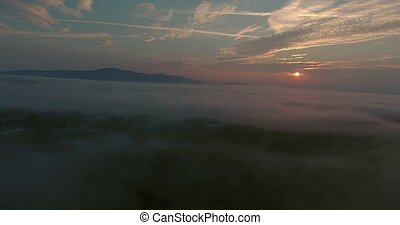 Aerial view of morning town covered by mist, sunrise -...