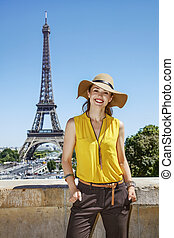 smiling woman in bright blouse in front of Eiffel tower in...