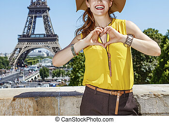 smiling woman showing heart shaped hands in Paris, France -...