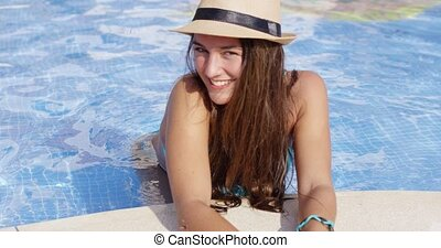 Smiling long haired beauty wearing bikini and hat stands in...