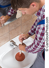 Plumber Using Plunger In Bathroom Sink - Close-up Of A...