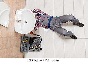 Male Plumber Lying On Floor Repairing Sink In Bathroom -...