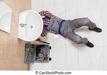 Male Plumber Lying On Floor Repairing Sink In Bathroom -...