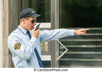 Male Security Guard Using Walkie Talkie - Young Male...