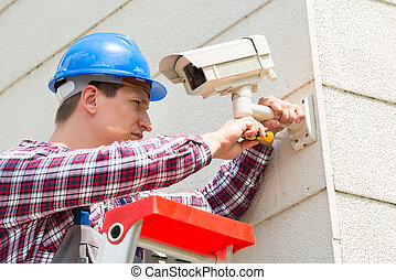 Technician Installing Camera On Wall - Young Male Technician...