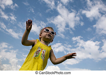little girl in a yellow T-shirt with sunglasses jumping on...