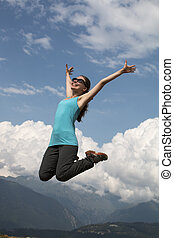 young happiness woman is jumping against blue sky. summer sunny day